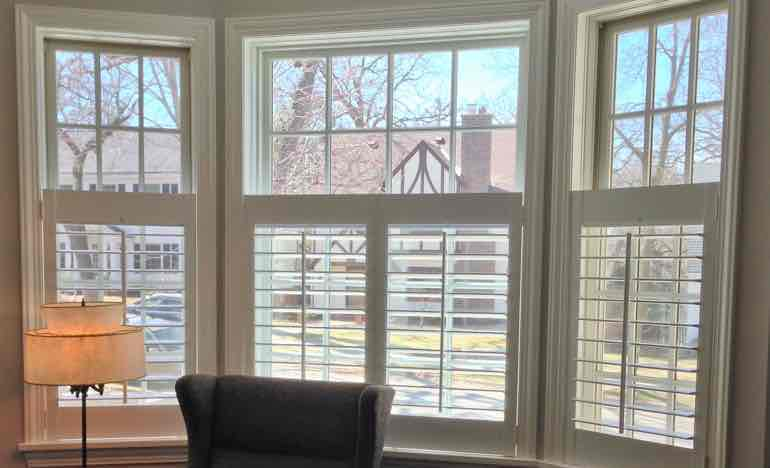 Bottom half plantation shutters in living room bay window.