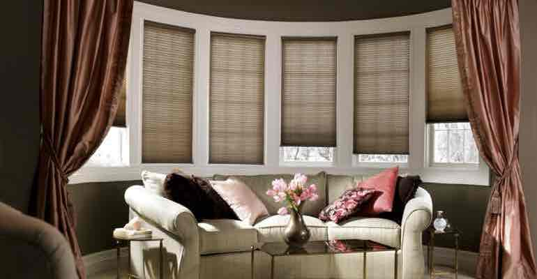 Vertical honeycomb shades in lounge bow window.