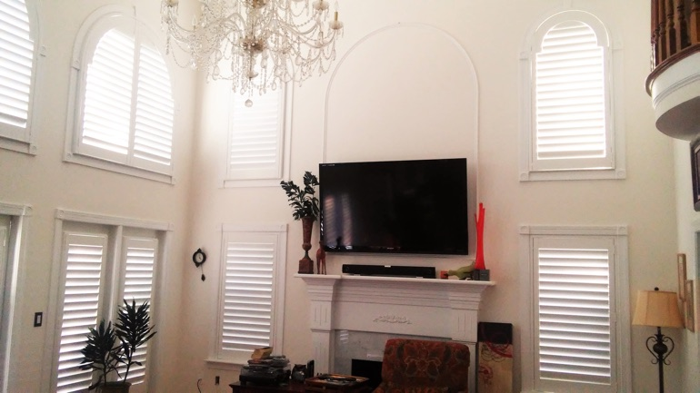 Fort Lauderdale great room with wall-mounted television and arched windows.