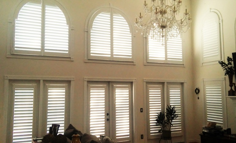 TV room in two-story Fort Lauderdale house with plantation shutters on arch windows.