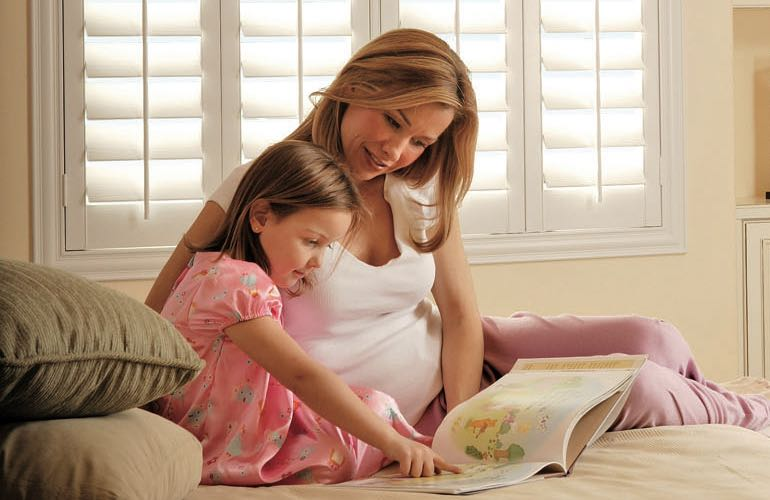 Mom and child reading on bed with shuttered windows.