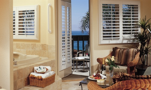 Plantation shutters on casement windows in a oceanfront house.