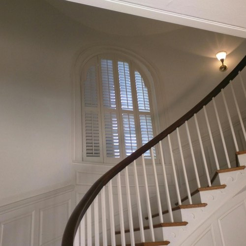White plantation shutters decorating arched window located in curved stairwell.