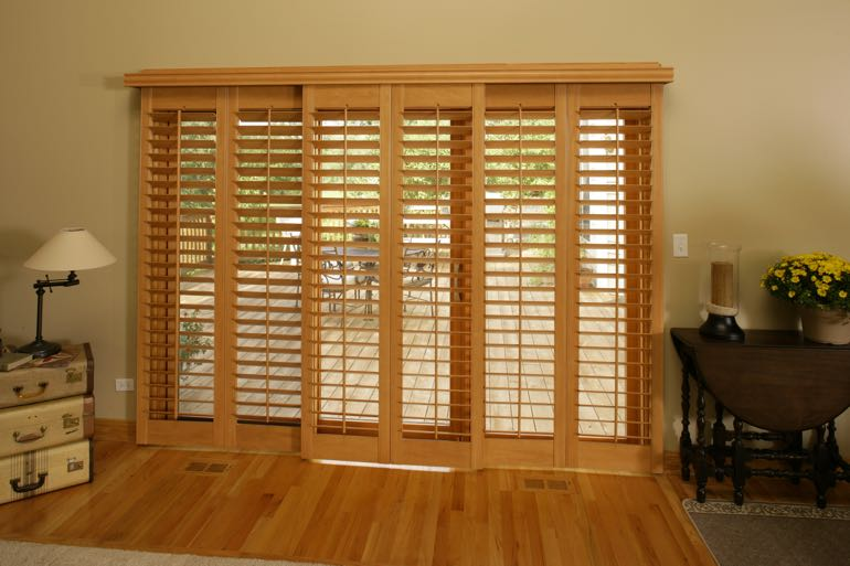 Faux wood shutters on sliding door connecting to back porch.