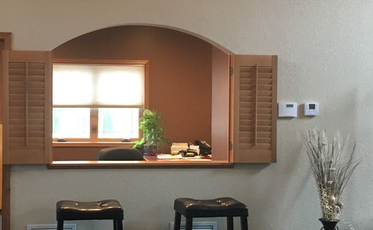 Wood shutters framing out a cutout between the kitchen and living room