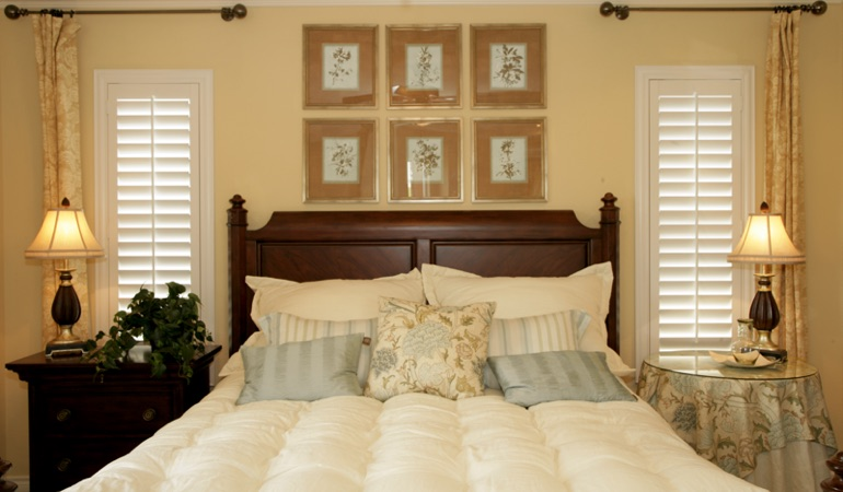 Bedroom with two tall plantation shutters on either side of bed in Fort Lauderdale