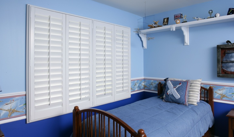 Large plantation shutters covering window in blue kids bedroom in Fort Lauderdale