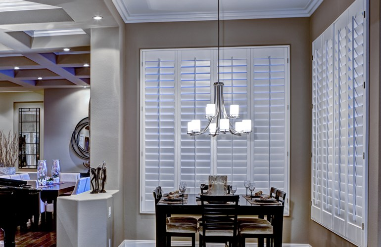 Modern dining room with white plantation shutters on two walls